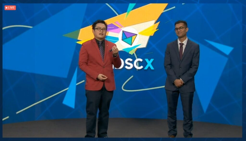 MDSCx Hosts stand in front of a LED screen